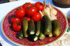 Traditional Russian pickled tomatoes, cucumbers and garlic on the festive tab - stock photo