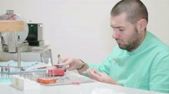 Dental technician using different tools sitting at his desk, dental care Stock Footage