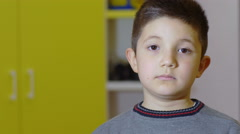 Portrait of a little boy looking in front of him, mouth closed, eyes opened Stock Footage