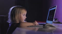 Little blond girl working on laptop in dark room at night Stock Footage