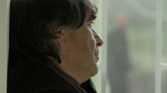 Wistful and nostagic man looking out the window, leaned at the wall Stock Footage