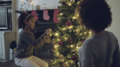 Mother and daughter decorating Christmas tree Stock Footage