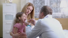 Angina. A pediatrician examines the throat of a little girl.  Stock Footage