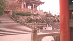 Moving shot up stairs into the courtyard of ancient temple in Kyoto Stock Footage