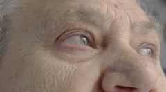 Detail of an old white woman looking aroudn, eyes opened, pupils, Stock Footage