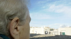 Back view of an aged woman looking the landscape of an ancient city, roofs Stock Footage