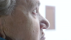 Profile of an aged grey haired woman, staring from the window Stock Footage
