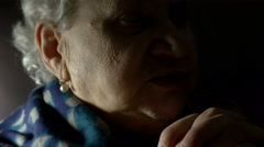 grey haired aged woman praying at home, recited rosary, believer - stock footage