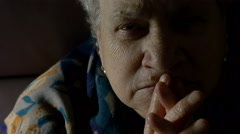 Grey haired aged woman praying at home, invocation, dark room, portrait Stock Footage