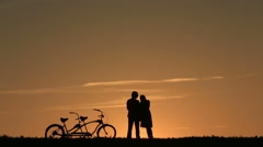 Silhouette of  Romantic Couple With Tandem Bicycle Stock Footage