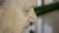 Profile view of an ager grey-haired woman, home scene Stock Footage