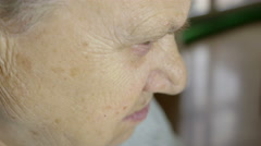 profile view of a retired woman looking absorbed and meditative - stock footage