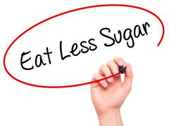 Man Hand writing Eat Less Sugar  with black marker on visual screen - stock photo