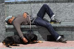 Homeless Man Sleeping on A Park Bench - stock photo