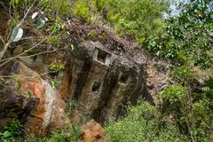 Traditional cave graves carved in the rock on the top of cliff.  Lemo is clif - stock photo