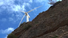 Wind turbine. The sky is covered with fluffy white clouds. Blades of grass - stock footage