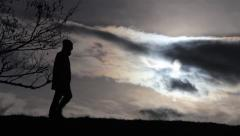 Unidentified person walks on a high embankment, lit by the rays of a sun  Stock Footage