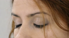Detail of white young woman opening her eyes and glancing Stock Footage