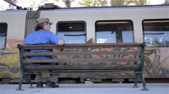 Man sitting on a bench in the station look to the left and right of people  - stock footage
