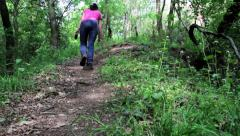 Young girl walking alone on a trail in a deciduous forest - stock footage