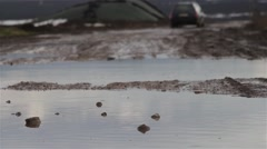 Car is lost in the distance, running on a road land full of huge puddles Stock Footage