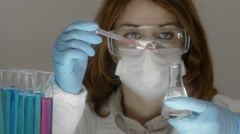 Skilled woman working for a chemical industry pouring drops of a new product Stock Footage