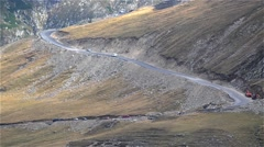 Column of cars running on paved mountain road that has many switchbacks  Stock Footage