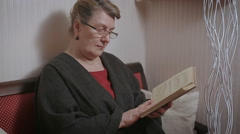 Elder woman reading a book at home Stock Footage