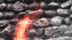 An old wall of stone, found in woods and beside him a consuming fire 1 - stock footage