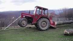 Tractor that pulls a cut tree trunk in the forest with a cable. Because weigh Stock Footage