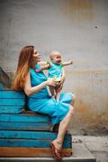 Cute Happy Toddler Sitting on Loving Mother`s Knees Stock Photos