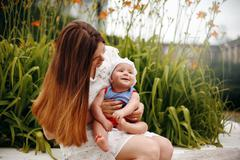 Cute Happy Toddler Sitting on Loving Mother`s Knees - stock photo