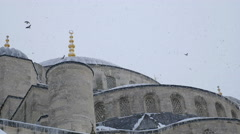 Snowstorm on a mosque in winter, birds flying in the sky Stock Footage