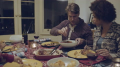 Mixed race family eating Christmas dinner - stock footage