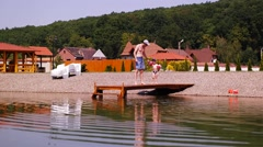 Father teach his son to jump off the dock into the lake - stock footage