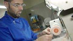 Man specialized in dental technology working at the lathe Stock Footage