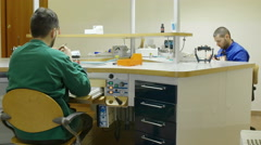 two specialized techinician working in a prosthodontic laboratory - stock footage