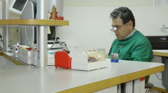 Dental technician sat at his desk, working with a specialized tool Stock Footage