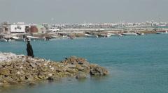 Arab woman throwing rocks into the sea, Manama, Bahrain Stock Footage