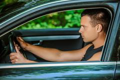 Portrait of young man driving car Stock Photos
