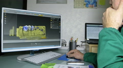 a dental care specialist uses a computer graphics to generate a denture model - stock footage
