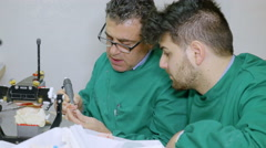 In a dental technology lab a trainee learn how work by skilled techinician Arkistovideo