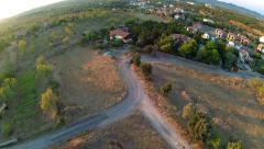 Aerial view of a car driving through village Stock Footage