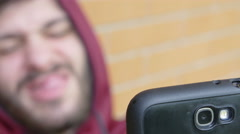 Drug addict plays with his smartphone, faces and selfies Stock Footage