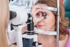 Professional female ophthalmologist is checking human eyes - stock photo