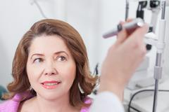 Experienced oculist is examining eyes of patient - stock photo