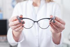 Cheerful female ophthalmologist is working with patient Stock Photos