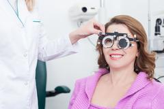 Skillful ophthalmologist with equipment for lens determination - stock photo