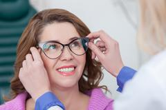 Professional oculist is giving eyewear to the lady - stock photo
