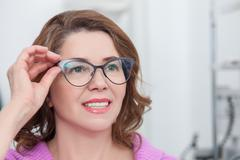 Cute lady is trying on eyewear in clinic Stock Photos
